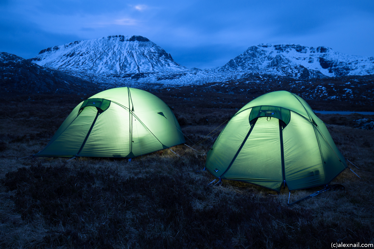 Torchlit tents with Ruadh Stac Mor and A'Mhaighdean behind
