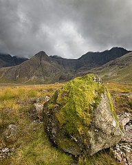 A massive boulder covered in moss with mountains behind at Coire na Creiche, Isle of Skye