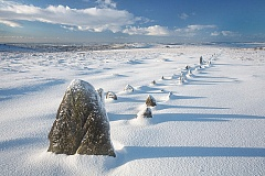 the main stone row of merrivale in freshly fallen snow with blue skies