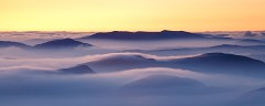 view from glyder ridge of temperature inversion over snodonian hills at sunrise