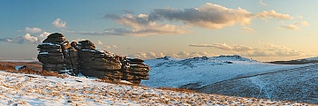 crow tor in the snow with the beardown tors in the distance shot at sunset