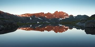 Ertenhelltinden reflected in a pool of water below Hermandalstinden at sunrise