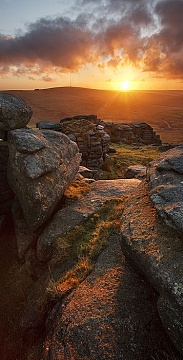 the sun rises over Staple Tor with granite lit up in the foreground.