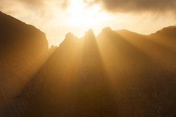sunrays burst through Kamman ridge in Lofoten, Norway