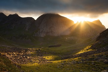 sunrays burst over a ridge in Lofoten Norway