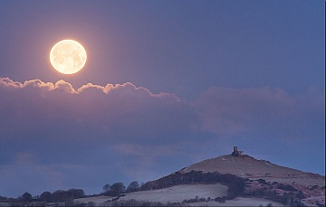 the moon setting at sunrise next to Brentor Church in Devon