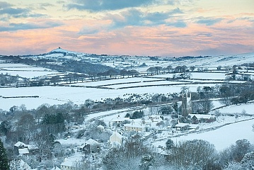 snow covering peter tavy and the surrounding area at sunrise
