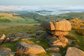 Roos Tor on Dartmoor at sunrise with mist below