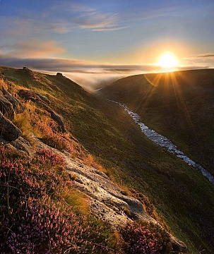 Tavy Cleave at sunrise with heather in the foreground and cloud drifting ont he horison and a full rising sun