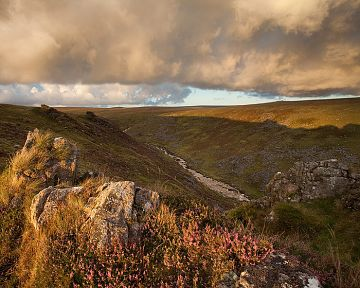 dark clouds form over tavy cleave at sunset