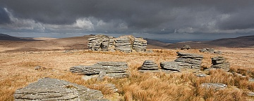 wild tor on Dartmoor lit by full sunshine under heavy clouds