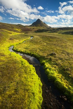 a small stream winds its way towards the peak of Storasula in Iceland